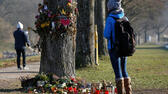 A woman looks at flowers and messages attached on a tree near the site where a 19-year-old female student died on October 15, in Freiburg, Germany December 6, 2016. REUTERS/Vincent Kessler Reuters
