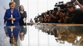 Photographers and television cameras cover German Chancellor Angela Merkel as she leaves a news conference in Berlin, Germany, Thursday, July 28, 2016. Second left is Angela Wefers, the journalist who led the news conference. (AP Photo/Markus Schreiber) AP