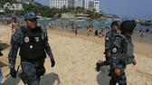 Federal police officer patrol Caleta beach crowded with local residents and tourists in Acapulco, Mexico, Friday, May 13, 2016. The city of Acapulco and Guerrero state in general have experienced a wave of violence attributed to warring drug gangs. On Saturday Mexican authorities say three men were gunned down, in a tourist-hotel quarter of the Pacific resort city. (AP Photo/Enric Marti) AP
