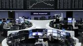 Traders work at their desks in front of the German share price index, DAX board, at the stock exchange in Frankfurt, Germany, April 4, 2016. REUTERS/Staff Reuters