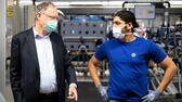 Lower Saxony's State Prime Minister Stephan Weil and a worker wear protective masks at the Volkswagen assembly line after VW re-starts Europe's largest car factory after coronavirus shutdown in Wolfsburg, Germany, April 27, 2020, as the spread of the coronavirus disease (COVID-19) continues. Swen Pfoertner/Pool via REUTERS Reuters